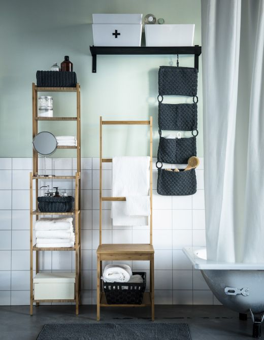 An image of a bathroom with a bathtub and storage including shelves, woven baskets and plastic bins.