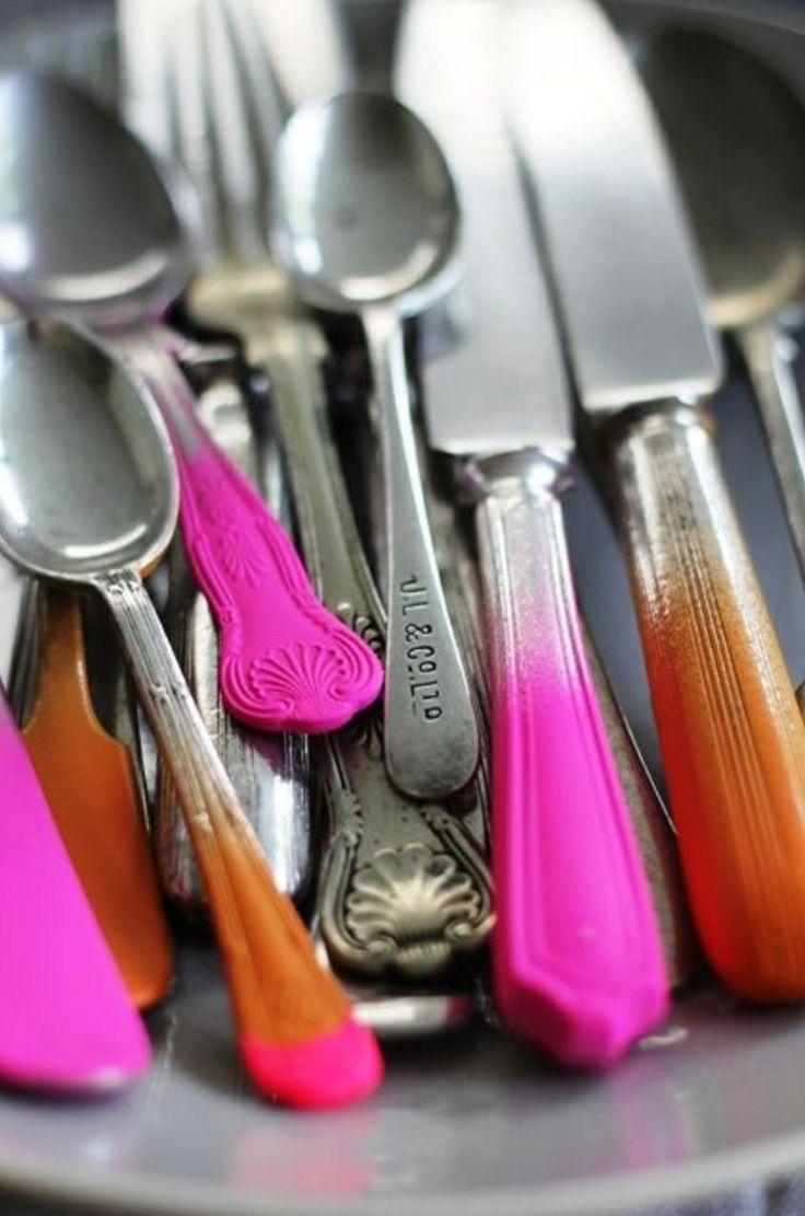 Cubiertos en hierro, naranja y fucsia. Hay tenedores, cucharas y cuchillos.