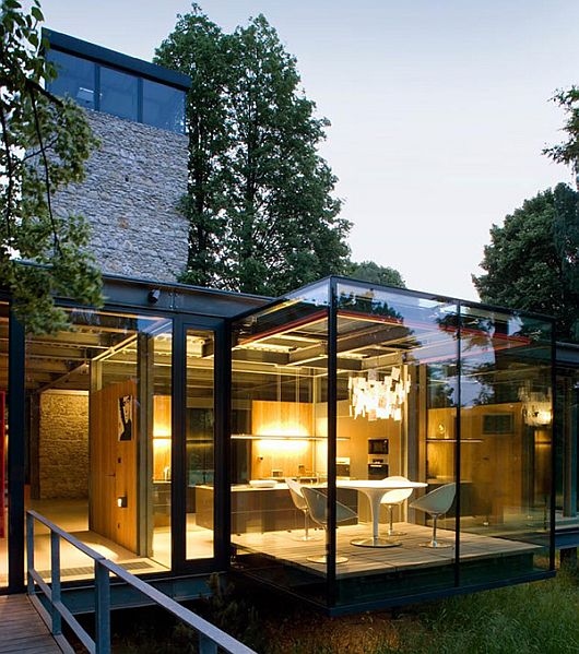 PCKO Architects The Jodlowa House near Krakow shines with its fully glazed facade, floating above the ground thanks to its steel frame. The modern glass house has indoor swimming pool, 2 bedrooms and 140 sq.m. living area and a five-story tower, consisting of guest rooms on the lower levels and a study on the top that offers extensive views. A mature tree was preserved by integrating it into the house thanks to openings in the ceiling and the floor.