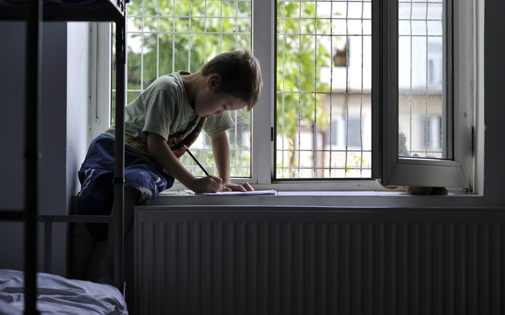 An Afghan boy sits on the window shelf and draws while staying in a reception centre in Radauti, Romania. © UNHCR/B. Szandelszky #asylum #Romania