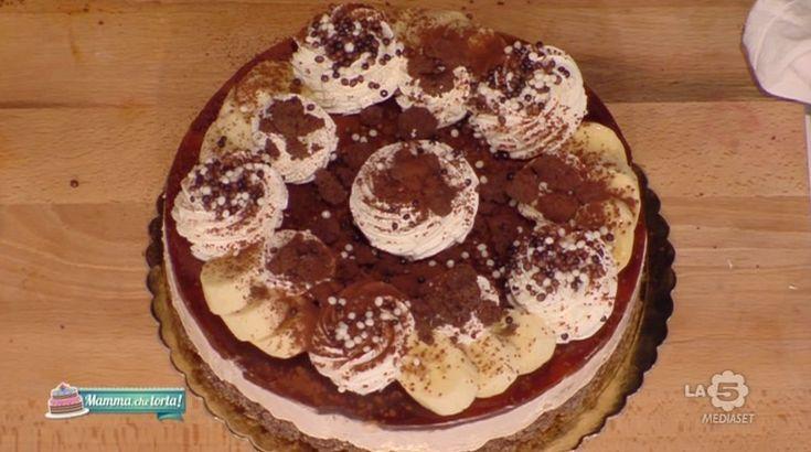 c2Impasto: 150 g burro, 160 g farina, 120 g zucchero di canna, 2 cucchiai di cacao amaro. Farcitura e decorazione: 400 g banane, 2 banane tagliate a rondelle, 1 busta di gelatina in fogli, 120 g zucchero, 3 buste di dolceneve, 600 ml panna, 200 g di guarnizione al caramello, 50 g di gocce di cioccolato, 1 busta di gel per torte, 125 ml acqua, 2 cucchiai di cacao amaro, 1 caffè espresso, decorazioni al cioccolato.