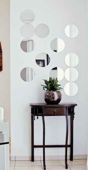 O arranjo de espelhos composto por doze plaquinhas, com 20 cm de diâmetro, ganhou espaço acima do aparador (cada jogo com quarto do modelo Fractal Slim, da Tok & Stok, sai por R$ 29,90).