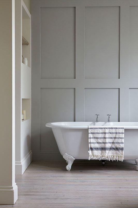 Klassisk badeværelse bestående af grå panelvægge, badekar på løvefødder og indbyggede hylder i væggen.