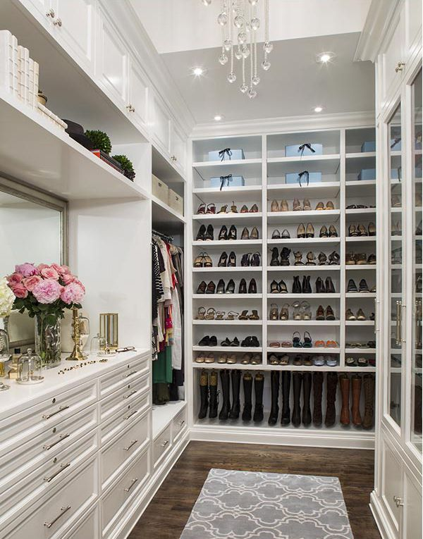 This elegant white closet has customized storage for boots, flats and heels on one long wall. A dresser with a large gilded mirror sits on the far wall, across from glass-faced cabinets. A long, modern chandelier hangs from the soaring ceiling.