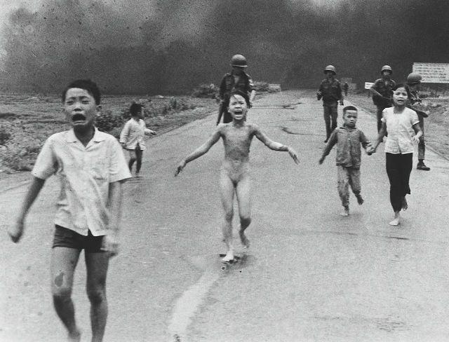 1972年 「Vietnam War (ベトナム戦争)」 南ベトナム軍の空軍機がを投下したナパーム弾から、裸で逃げる9歳の少女ファン・ティー・キム・フックたち。「戦争の恐怖」と題された写真。