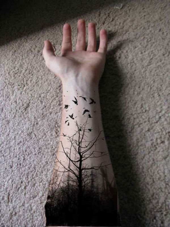 When it comes to tattoos, why not be inspired by your favorite photograph? We love this tattoo because it's placement is pretty unique. It takes inspiration from the traditional sleeve design, but incorporates a black and white photograph into the design to add that extra artistic touch. We also love how the tree branches almost resemble veins.