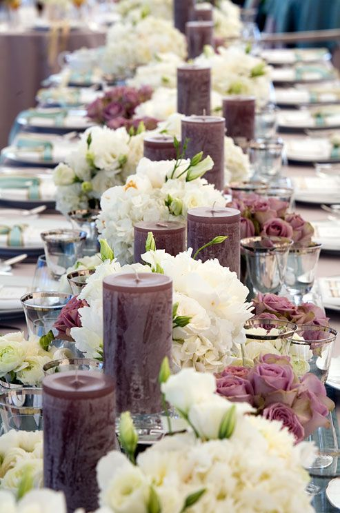 Long tables set with white and dusty pink roses and white peonies in full bloom are accented with tall purple candles
