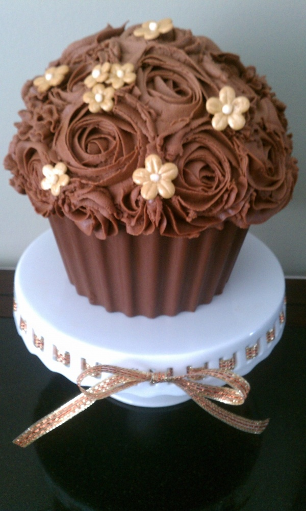 Chocolate giant cupcake with buttercream roses, gold blossoms and chocolate cupcake liner.