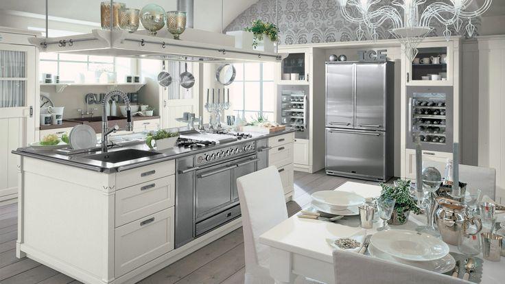 Cucina collezione English Mood con isola, finitura Bianco Gesso. L%u2019isola dispone di piano in acciaio satinato provvisto di tagliere, canale attrezzato , piano cottura con fry-top, blocco cottura dotato di due forni.