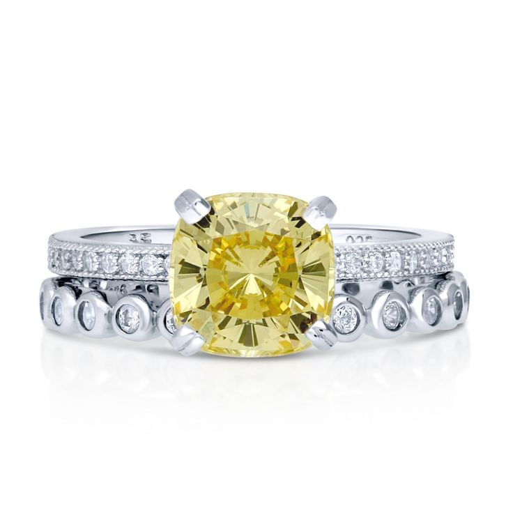 """This 2-piece solitaire ring set is the duo that every girl will say """"yes"""" to. The high setting and bold color is what makes it so outstanding. Made of rhodium plated fine 925 sterling silver. Features 2.04 carat cushion cut canary yellow cubic zirconia (8mm) in 4-prong setting. Accented with 0.485 ct.tw round cut cubic zirconia in bezel and micro pave setting. Bands measure 4mm in width."""