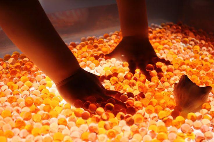 Experimentant a la taula de llum amb perles d'aigua de colors.