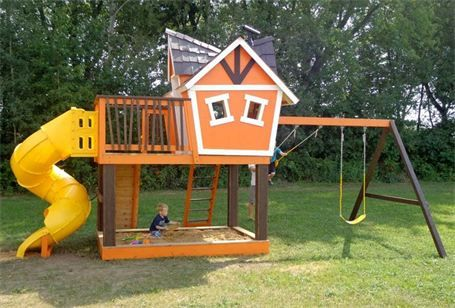 Elevated Orange Playhouse (front side) : This was a custom built double dormer playhouse with a crooked smokestack, tunnel slide, sandbox, climbing wall and swings.