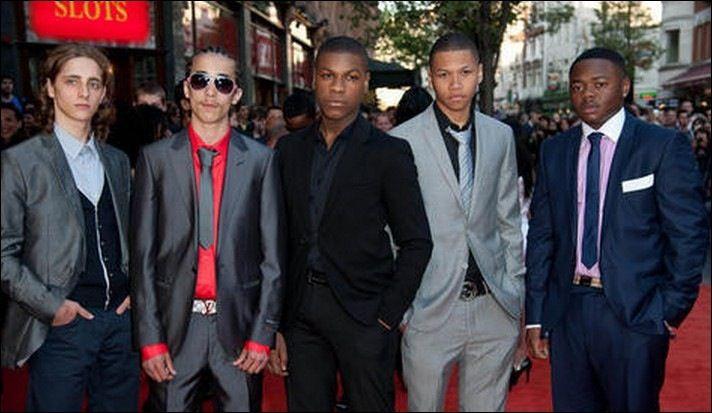 "John Boyega in black suit with fellow cast members of hit film ""Attack The Block"""