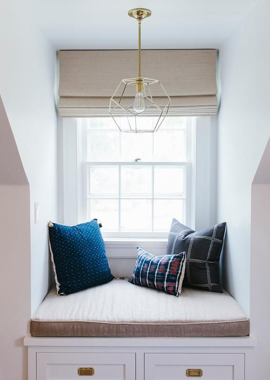 Bedroom dormer window alcove is filled with a built-in window seat fitted with two drawers adorned with brass hardware illuminated by a brass polyhedron pendant.