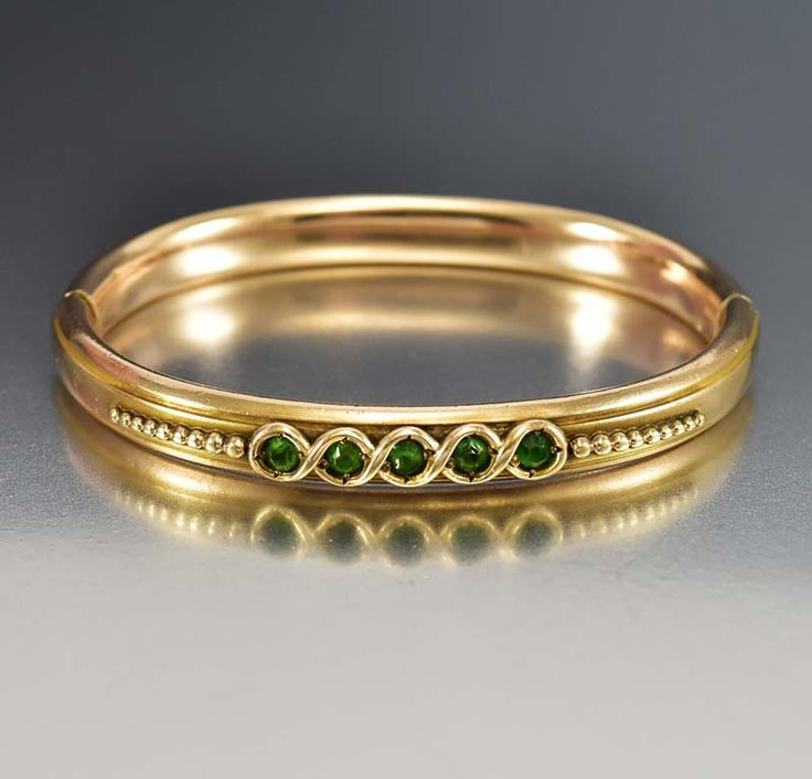 Victorian gold filled bangle bracelet with sparkling emerald glass front creates this classic antique from the turn of the 19th century. The band of the bangle is a rose gold fill with a yellow gold f
