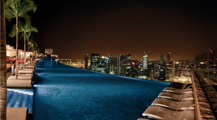 Rooftop pool at Marina Bay Sands, Singapore. The infinity pool in this hotel is elevated at 55 stories up which is more than 200 meters from the ground. Aside from the height, the beauty of the pool would really make anyone's head spin because it allows guests to enjoy the sight of towering Singapore buildings. Amazingly, intricate architecture allowed the hotel to create a huge pool. The measurement of their infinity pool is equivalent to three Olympic size pools put together.