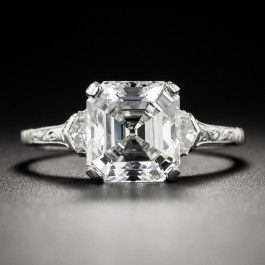 Behold! This bright icy-white, ultra-sparkling 2.91 carat vintage emerald-cut (a.k.a. Asscher-cut) diamond beaming between a pair of fancy step-cut pentagonal epaulet diamonds. The consummate, elegantly understated Art Deco mounting, circa 1930, is hand fabricated in platinum and is modestly adorned with hand engraved details. A majestic classic for a majestic, classic, and very lucky lady. Cur
