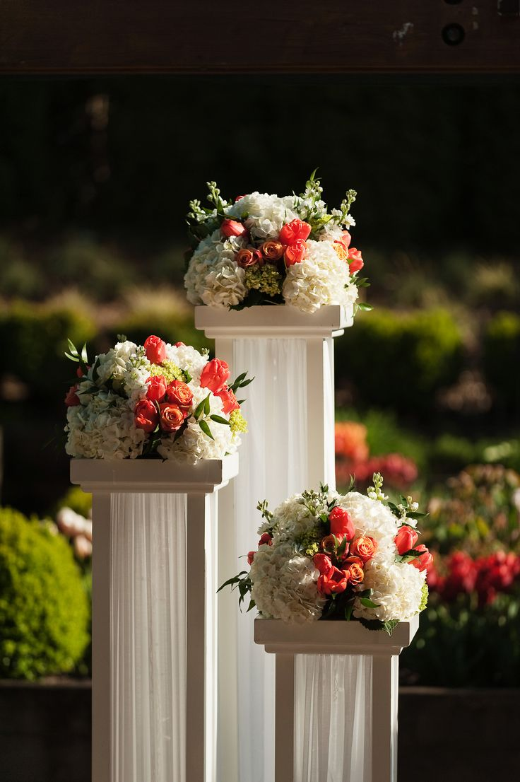 Vari-height columns topped with bright orange floral arrangements -  outdoor wedding at Willow Lodge. Read the touching story here: http://www.StyleMePretty.com/2014/05/23/seattle-wish-upon-a-wedding-vow-renewal/ Kimberly Kay Photography - www.kkayphoto.com - Floral Design: JensBlossoms.com - Wedding Planning: Vows Wedding & Event Planning vowswedding.com
