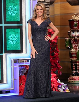 JOVANI Gunmetal re-embroidered lace gown enhanced in sequins, wide v-neckline, slightly off shoulder cap sleeves, flared hemline w/train | Vanna White's dresses | Wheel of Fortune