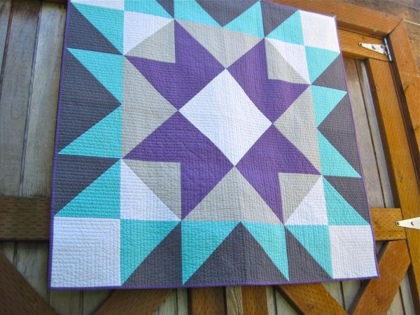 A quilt made up of one huge block, much like the designs painted on barns -- seen on sewkatiedid blog.