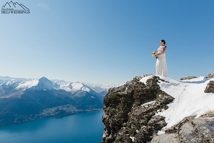 Bride stands on The Ledge. Destination Heli weddings Queenstown.