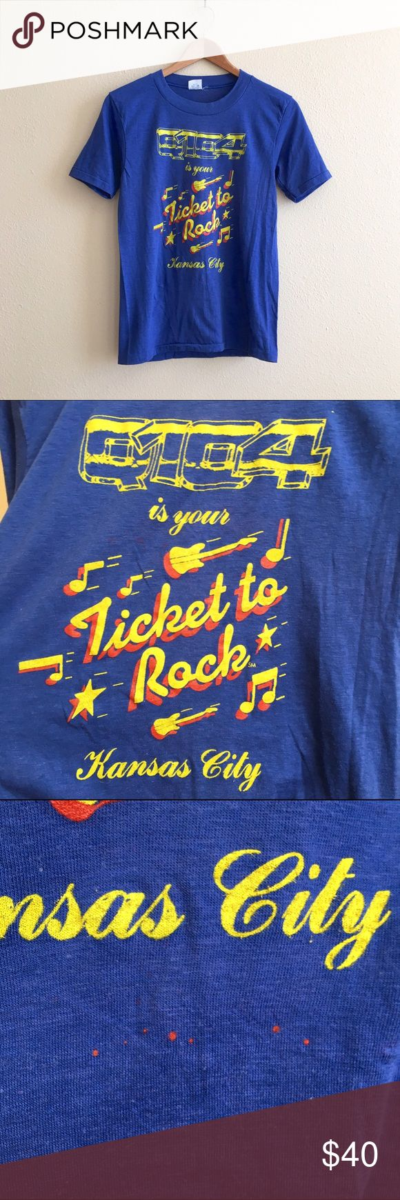 "Kansas City Paper Thin Radio Tee Paper thin royal blue tee from country radio station Q104, ""Ticket to Rock"" Kansas City. There are a few red spots shown in photos that are a result of the graphic printing a little sloppy.   BRAND: Mayo Spruce MATERIAL: 50/50 YEAR/ERA: 70s LABEL SIZE: M BEST FIT: XS/S  MEASUREMENTS: Chest 16.5 inches  Length 25 inches    I do not model or trade, sorry!  Check out my closet for more vintage! Vintage Tops Tees - Short Sleeve"