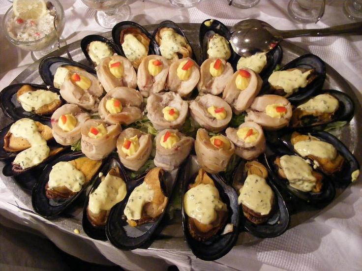 en el plato hay almejas a la parmesana que es la almeja en su concha con aderezo de pimienta y luego queso encima que se derrite y locos un marisco chileno