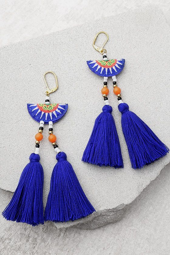 """Join the party in the Shashi Camilla Blue Tassel Earrings! A green, coral, white, and blue embroidered bead with gold, black, white, and coral beads tops trendy blue tassels. Earrings measure 5"""" long."""