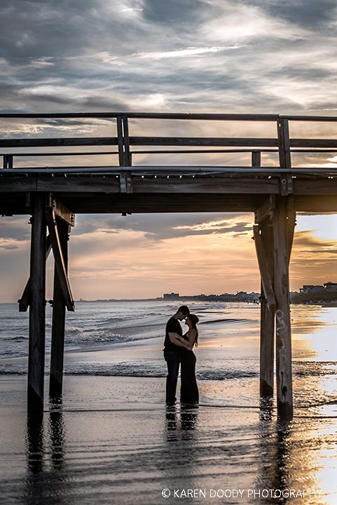 Newly engaged couple framed by fishing pier during sunset at Atlantic beach