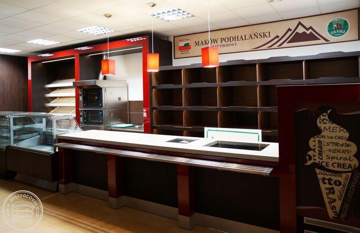 Wyposażenie sklepu spożywczego: lada obsługi w ciągu z witrynami, za ladą szafki, regały na pieczywo z boksami na bułki, regały na alkohol z dolnymi szufladami wbudowane w okładziny ścian, wykonane z płyt meblowych, laminatów HPL, drewna, blaty materiał SSV typu Corian.
