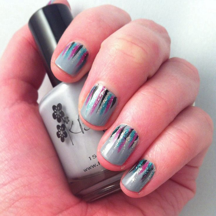 Grey nails with free hand painted glitter lines.