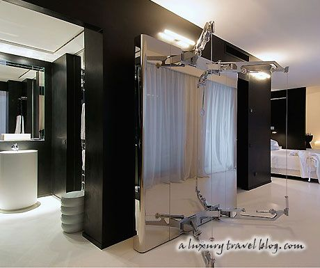 This contemporary space features the multi-purpose Kinesis exercise machine by Technogym, an extra large hot tub next to its king-size bed and a contemporary bathroom, all black & white.
