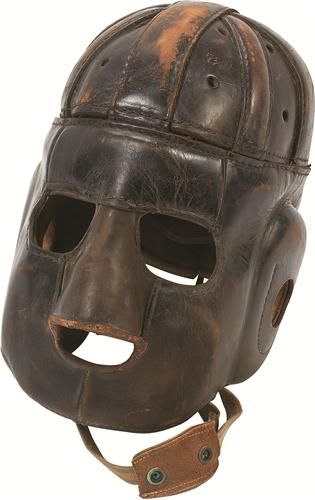 "1920s Executioner's Football Helmet (MEARS LOA - U of Michigan). This football helmet from the 1920s was recently discovered in an attic trunk in Ann Arbor, MI, in a house close to the University of Michigan campus. ""Spalding"" is in a circular incised stamp on the front of the helmet and size 7 1/8 on the front left panel.  $11,692"