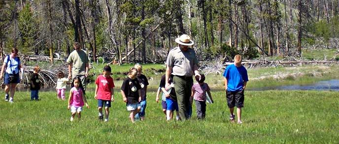Ranger walking with a group of children.   We offer a variety of ranger programs, walks, and talks in locations throughout the park year-round. Schedules are available below by season. The previous year's schedules are here to help you plan your trip, as similar programs are offered seasonally each year.  Link to 2015 list. UPDATED FOR 2016