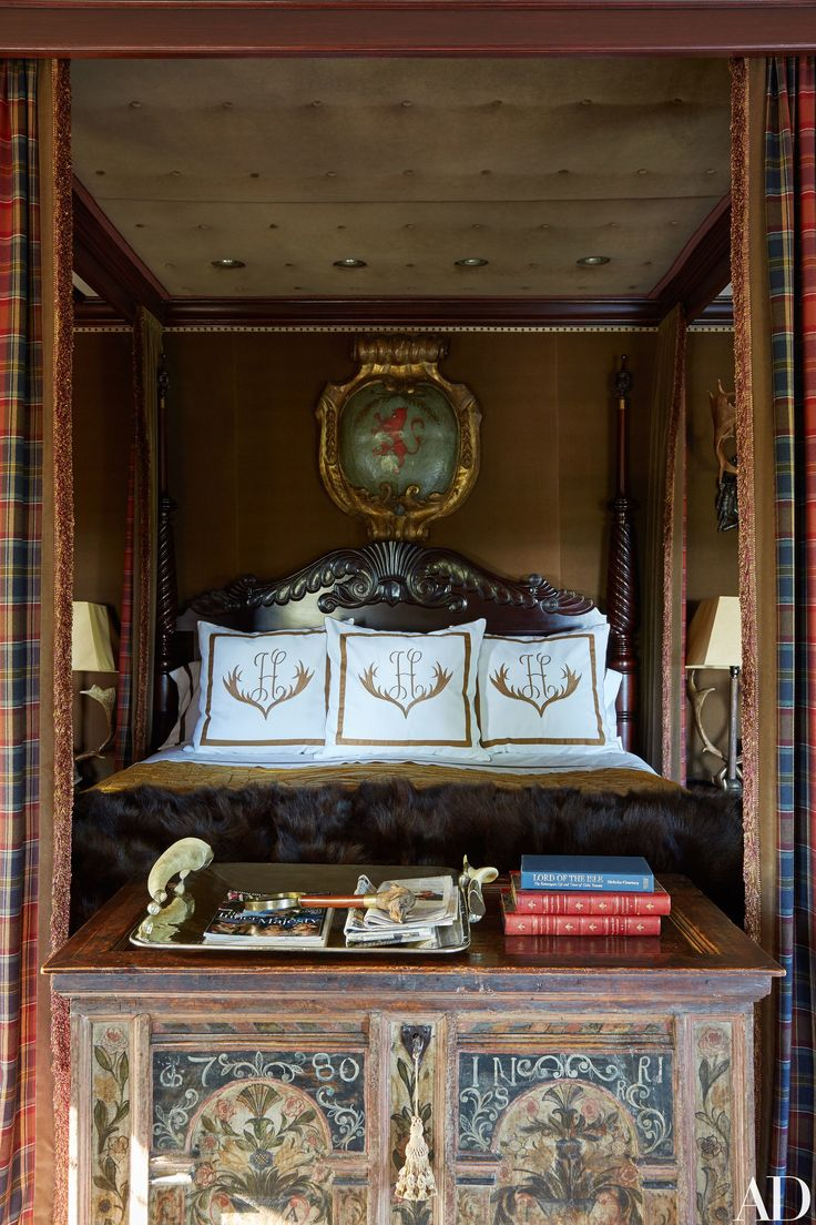 The master bedroom boasts an English mahogany four-poster, an antique Italian armorial shield, and a painted Bavarian chest. Embroidered bedding by Leontine Linens.