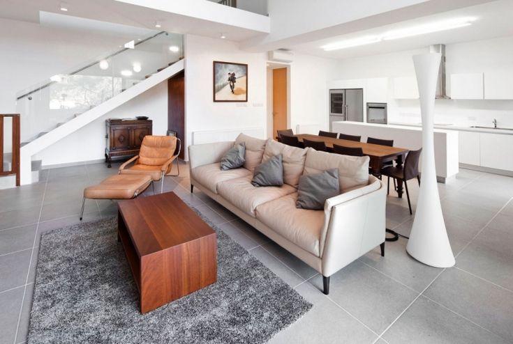 carrelage gris clair, canapé droit en cuir beige et table à manger en bois massif