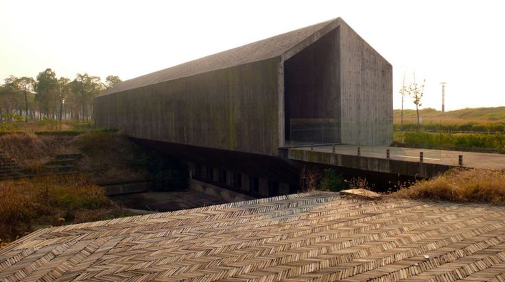 """Resembles a traditional farmhouse or industrial shed, but its textured concrete façades and adjacent sunken courtyard are characteristically cloaked with sociopolitical metaphor...'.'accelerating modernization has literally stripped away the foundation of traditional society."" [""Archeological Archive,"" Jinhua Architecture Park 