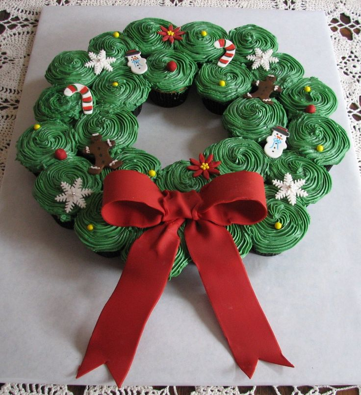 Christmas cupcake wreath - It seems everyone likes to make these cupcake wreaths for Christmas. They are a lot of fun and fairly easy. I added fondant accents on it, along with a large fondant bow. Thank you for looking and Merry Christmas!