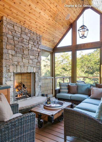 A look inside the second-story screened-in porch, which has a vaulted knotty pine ceiling and a stone surround on the fireplace.
