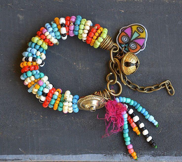 Deze armband is bedekt met kleine Parel ringen in vele kleuren. Één zijde is afgewerkt met een vintage Kuchi knop en een kraal kwast. Hij is versierd met een Indiase brass bell en het is aanpasbaar aan de meeste polsen. U ontvangt een soortgelijke armband van degene die u ziet in de afbeelding.