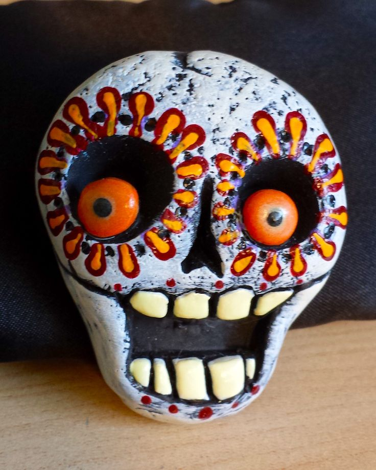 Wacko Day of the Dead Skull Pin! Durable polymer clay skull, painted in bright autumn oranges and black, with glow in the dark eyes and teeth. By Ellie Gee  MacabreWebs Studios 2015