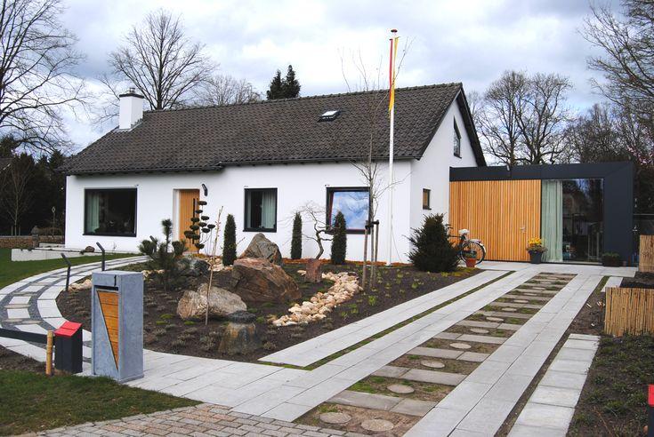 Effect wit stuken, donkere kozijnen en nieuwe houten garagedeur en voordeur