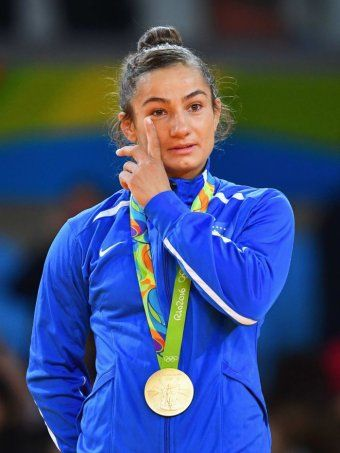 Majlinda Kelmendi wipes away a tear on the podium after winning Kosovo's first ever gold medal in  the Olympics, in judo at the 2016 Rio Olympics