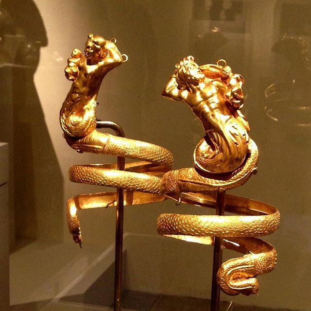 An impressive pair of ancient, gold serpent armbands featuring a male & female Triton, Greek, ca. 200 BC. Each Triton (sea creature) holds a small winged Eros, the Greek god of love, and would have been worn by a wealthy citizen of the Hellenistic period. The small loops at the top were attached to the sleeve or shoulder of a garment to prevent them from falling down the arm, due to their weight. 💛 These pieces were absolutely stunning and I could just imagine the splendor of that period…