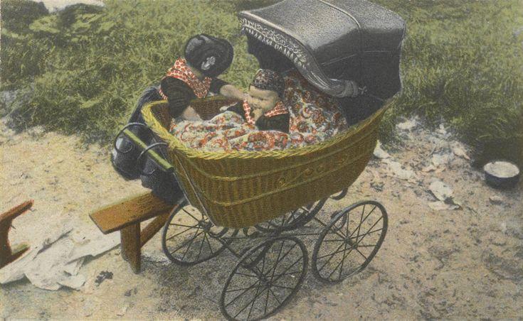 Twee meisjes in Staphorster streekdracht. In de kinderwagen zit klein meisje en naast de kinderwagen staat een bankje waarop een wat ouder meisje staat. De kinderwagen heeft een bak van gevlochten materiaal. Het oudere meisje draagt de 'nette', de zwarte kindermuts met opstaande rand en decoratieve haak aan de rechterzijde. Het meisje in de kinderwagen draagt een mutsje van gebloemde stof. 1905-1948 #Overijssel #Staphorst
