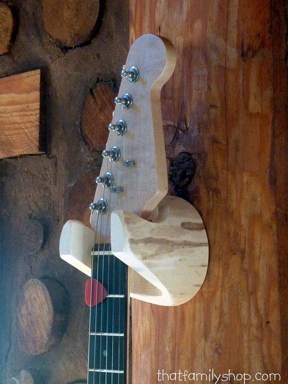 Elegantly carved from a solid log, this guitar hanger is sturdy, practical and beautiful. Untreated Aspen wood is strong, but soft enough to avoid leaving dents on your instruments neck. Measures approx. 4 x 4 and includes two screws for installation. Neck slot measures 2, and will accommodate other instruments as well, such as banjos, mandolins, ukuleles, etc. Please measure your instruments neck to verify fit; we can change the opening size if needed.  NOTICE TO INTERNATIONAL CUSTOMERS…