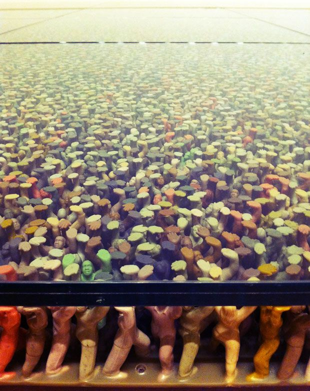 "FLOOR INSTALLATION BY DO HO SUH The installation takes of thousands of multicolored plastic toy figures ""holding up a large glass plate that can hold the weight of people across the glass."""