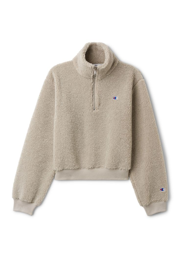 The Flow Sherpa Turtleneck by Champion is a short sweatshirt in a soft teddy material. A turtleneck with a zipper, an elasticated ribbed hemline and subtle
