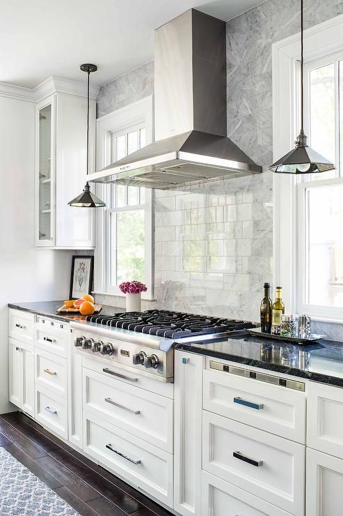 Black And White Kitchen Features White Cabinets Paired With Black Marble  Countertops And A White Marble Subway Tiled Backsplash.