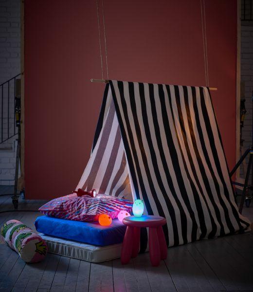 Uma tenda de tecido às riscas com muitas almofadas, um banquinho e algumas…